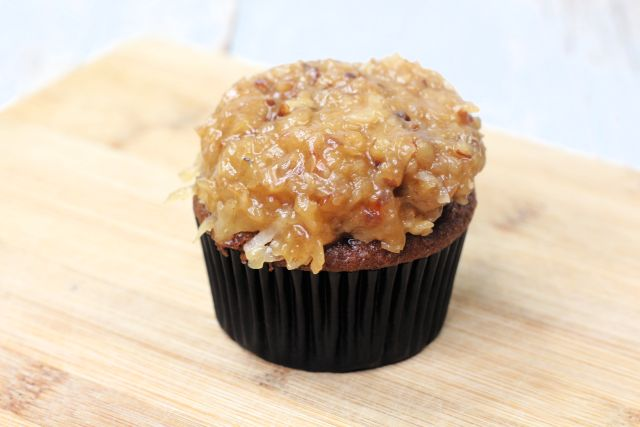 Building the German Chocolate Cupcakes adding the coconut pecan frosting to them